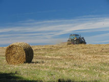 Tractor in Field. A tractor working in a field with a bale of straw in the foreground Stock Photography