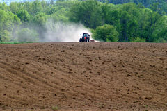 Tractor in field. Grooming the ground Royalty Free Stock Photography