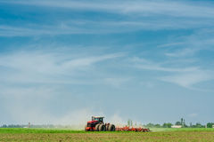 The tractor in the field. On the background of blue sky Stock Photos