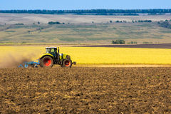 Tractor in the field of clean wheat crop.  Royalty Free Stock Photo