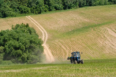 Tractor in a field in early summer Royalty Free Stock Photos