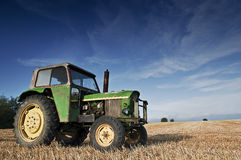 Tractor in a field of grain. Tractor in a field of freshly mowed cereal Stock Photography