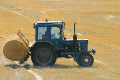Tractor in a field of hay Stock Photo