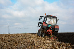 Tractor in the field in the middle of tillage Royalty Free Stock Photo