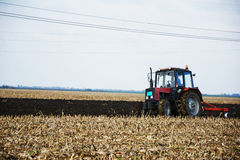 Tractor in the field in the middle of tillage Stock Photo