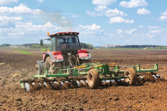Tractor on the field. Tractor plowing the field in spring day Stock Images