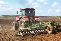 Tractor on the field. Tractor plowing the field in spring day Stock Photo