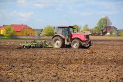 Tractor on the field. Tractor plowing the field in spring day Stock Image