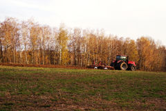 Tractor in the field plows the earth in autumn. Tractor in the field plows the earth in sunny autumn day Stock Photo