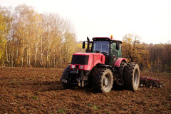 Tractor in the field plows the earth in autumn. Tractor in the field plows the earth in sunny autumn day Royalty Free Stock Image