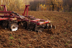 Tractor in the field plows the earth in autumn. Tractor in the field plows the earth in sunny autumn day Royalty Free Stock Photo