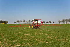 Tractor on field sputtering pest Royalty Free Stock Photos
