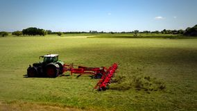 Tractor field two setting fly over. Tractor drives over green field stock footage