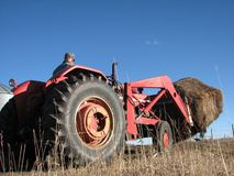 Tractor with Front-end Loader. A picture of a farm tractor with a front-end loader in use transporting a big round bale. Blue sky background Royalty Free Stock Image