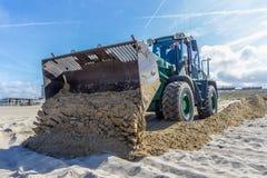 Tractor Front End Loader moving sand. Kijkduin, the Netherlands - April 6, 2017: Tractor Front End Loader moving sand royalty free stock images