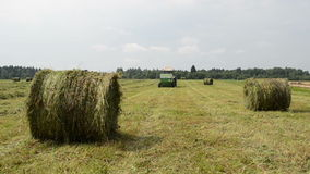 Tractor gather hay bale. Straw bales and agricultural tractor collect gather hay in field near rural village houses stock footage