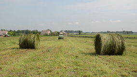 Tractor gather hay bale Stock Photos
