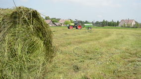 Tractor gather hay bale Stock Images