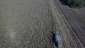 Tractor gathering field sowing, aerial view of a field with a tractor picking up the crop stock footage