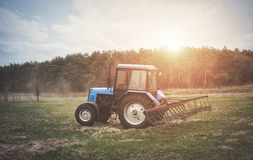 The tractor goes and pulls a plow plowing a field before landing of crops. Royalty Free Stock Photos
