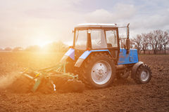The tractor goes and pulls a plow,plowing a field before landing of crops. Royalty Free Stock Image