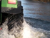 Tractor going by flood road Stock Image