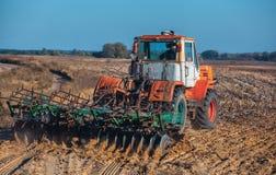 Tractor grande, viejo, hermoso que ara la tierra en el campo después de girasoles de la cosecha del otoño de la cosecha Fotos de archivo