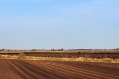 Beautiful earth. Tractor handles Latvia`s black land for planting Royalty Free Stock Photos