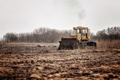 Tractor with ground. Tractor handles Latvia`s black land for planting Stock Photos