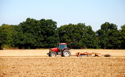 Tractor and harrow cultivating the soil Royalty Free Stock Photo