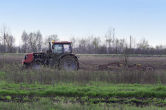 Tractor with harrow the field. Red tractor on the background of forest and cloudy spring sky harrow handles field stock photography