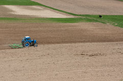 Tractor Harrowed Field. A tractor prepares arable field soil with harrow tool for sowing in springtime in Lithuania Royalty Free Stock Image