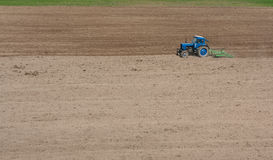 Tractor Harrowed Field. A tractor prepares arable field soil with harrow tool for sowing in springtime in Lithuania Stock Photos
