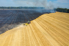 Tractor harrowing the field in fire Royalty Free Stock Image