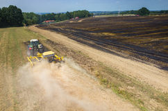 Tractor harrowing the field in fire Stock Photo