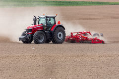 Tractor harrowing the field. The tractor harrowing the large brown field in spring season Stock Photography