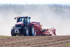 Tractor harrowing the field. The tractor harrowing the large brown field in spring season Royalty Free Stock Photography