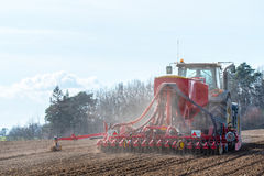 Tractor harrowing the field. Large view on the tractor harrowing the field in spring season Royalty Free Stock Images