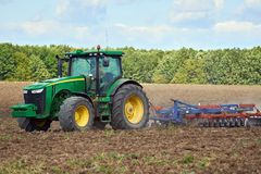 Tractor harrowing the field. Tractor harrowing plowed fields for autumn agricultural works Stock Image
