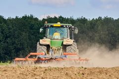 Tractor harrowing the field. Tractor harrowing plowed fields for autumn agricultural works Royalty Free Stock Photo