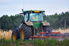Tractor harrowing the field. Tractor harrowing plowed fields for autumn agricultural works Royalty Free Stock Photos