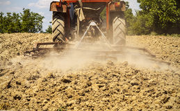 Tractor harrowing the land Stock Photo
