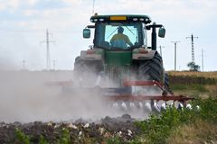 Tractor harrowing the field. Tractor harrowing plowed fields for autumn agricultural works Stock Images