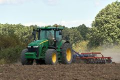 Tractor harrowing the field. Tractor harrowing plowed fields for autumn agricultural works Stock Photos