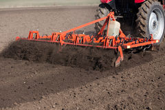 Tractor harrowing soil in spring Royalty Free Stock Image