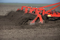 Tractor harrowing soil in spring. Tractor harrowing soil in preparation process for seeding in the field. Farming concept Stock Photos