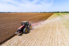 Tractor harrownig het grote bruine gebied stock afbeelding