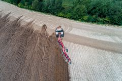 Tractor harrownig the large brown field royalty free stock photos