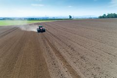 Tractor harrownig the large brown field stock image