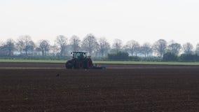 Tractor harrows a plowed field stock video